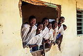 Schoolchildren looking out of a hole in the wall of a school where the window should be.