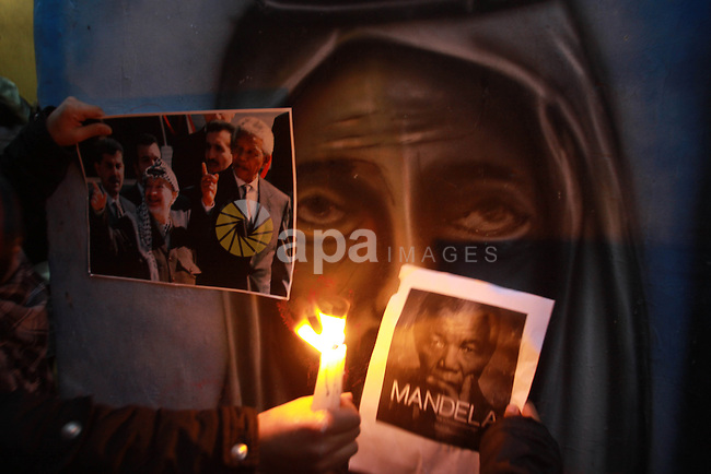 Palestinians light candles and hold placards depicting former South African President Nelson Mandela in the West Bank refugees camp of Balata near Nablus December 7, 2013. South African anti-apartheid hero Mandela died peacefully at home at the age of 95 on Thursday after months fighting a lung infection, leaving his nation and the world in mourning for a man revered as a moral giant. Photo by Nedal Eshtayah
