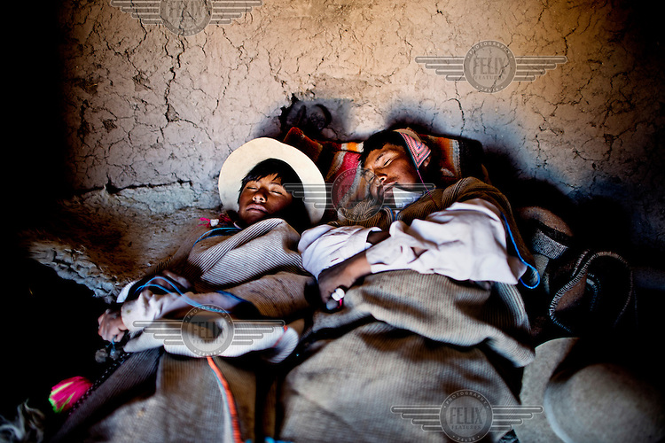Jose and Eloi rest after a hard day on the altiplano in their traditional circular Chipaya house.