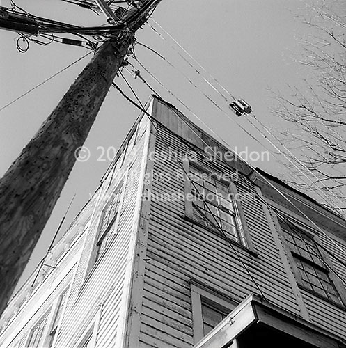 Upper floor of old white wooden building and utility pole<br />