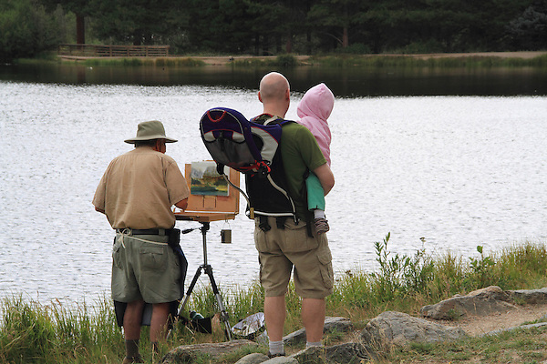 Senior citizen paints a landscape, as father and daughter watch, Rocky Mountain National Park, Estes Park, Colorado. .  John offers private photo tours in Denver, Boulder and throughout Colorado. Year-round.