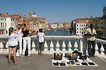 Venice Italy 2009. Grand Canal. Two women having their phograph taken by their daughter on the Ponte degli Scalzi.