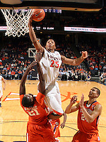 Feb. 2, 2011; Charlottesville, VA, USA; Virginia Cavaliers forward Akil Mitchell (25) shoots over Clemson Tigers forward Bryan Narcisse (21) and Clemson Tigers forward Milton Jennings (24) during the game at the John Paul Jones Arena. Virginia won 49-47. Mandatory Credit: Andrew Shurtleff