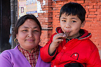 Nepal, Patan.  Mother and Son, Eating Chocolate.