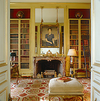 A striking portrait of the Duchess of Windsor by Gerald Brockhurst dating from 1939 is displayed above the red marble fireplace in the library