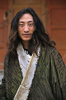 Khampa nomad in Labrang, Amdo Tibet.<br /> The Khampas, from the eastern Kham region are often seen wearing long braids adorned with red tassels and coins tied to the top of their heads. They walk with bravado as their silver ornate knives swing from their waists. When the Chinese first began their slow but steady infiltration into eastern Tibet in 1949 it was these brave nomadic warriors who fiercely wielded their swords to protect their land and their newly instated Tibetan leader, the young fourteenth Dalai Lama and aid him into his escape into exile in India. Some 130,000 refugees soon followed, but nearly six million were left behind.