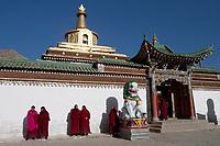 Tibetan monks stand outside of Labrang (Chinese Name - Xiahe) Monastery on the Qinghai-Tibetan Plateau. China.