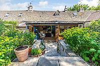 BNPS.co.uk (01202 558833)<br /> Pic: Strutt&Parker/BNPS<br /> <br /> Pitcured: Garden steps leading to living space. <br /> <br /> An 18th century cottage in 'the prettiest village in England' is on the market for £675,000.<br /> <br /> Number 2 School Lane is Grade II listed, built with beautiful Cotswold stone and filled with character features like exposed timber beams and original fireplaces.<br /> <br /> The attractive three-bedroom property is in the highly sought after Wiltshire village of Castle Combe.<br /> <br /> The quintessentially English village has been used regularly as a film location and the houses are mostly made with honey-coloured Cotswold stone.