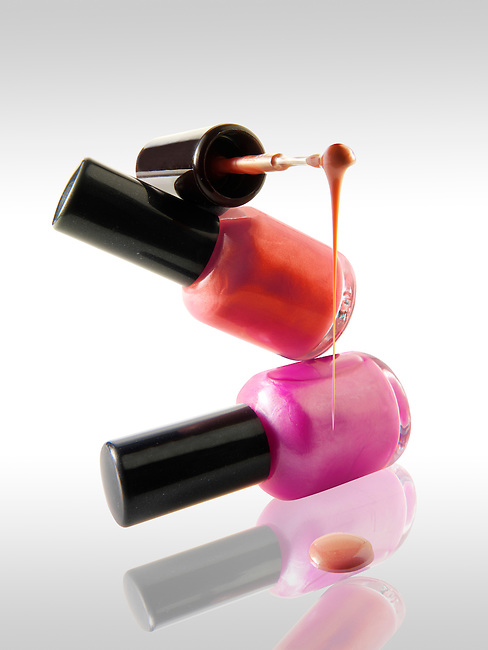 2 Nail varnish bottles balanced on each other in a fun way with a nail varnish brush balanced ontop dripping nail varnish.