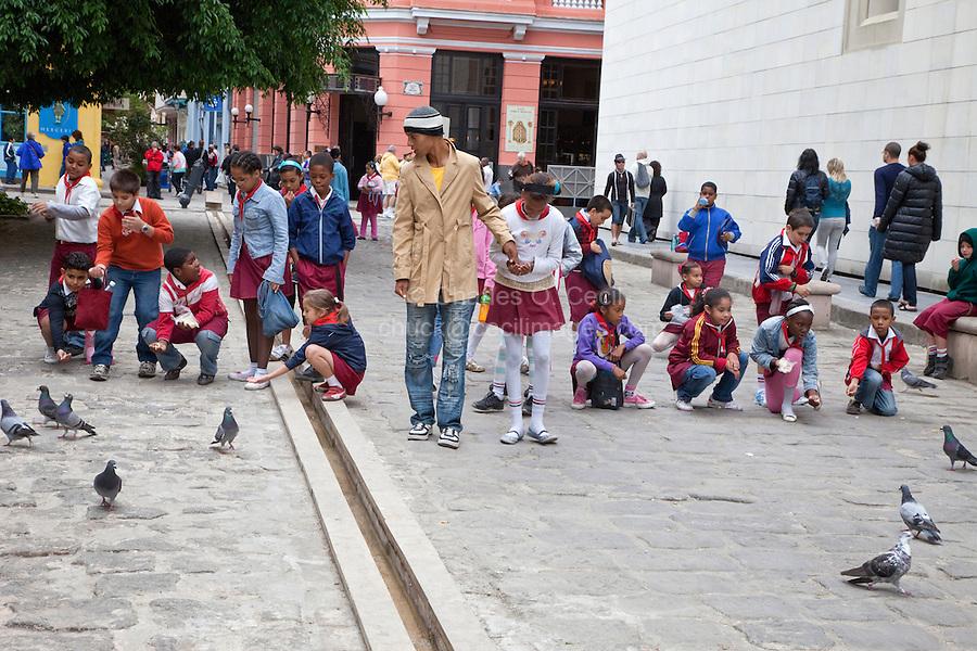 Cuba, Havana.  School Children Feeding Pigeons in the Street.
