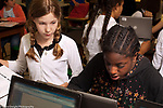 Public elementary school for gifted children grades K-6: two 6th grade girls use laptop computer to research in class