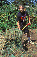 Cleanup in the garden with man person using tool fork rake