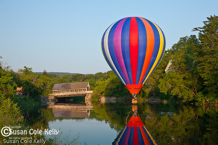 A hot air balloon reflected in the Ottaquechee River in Quechee village, Hartford, VT, USA