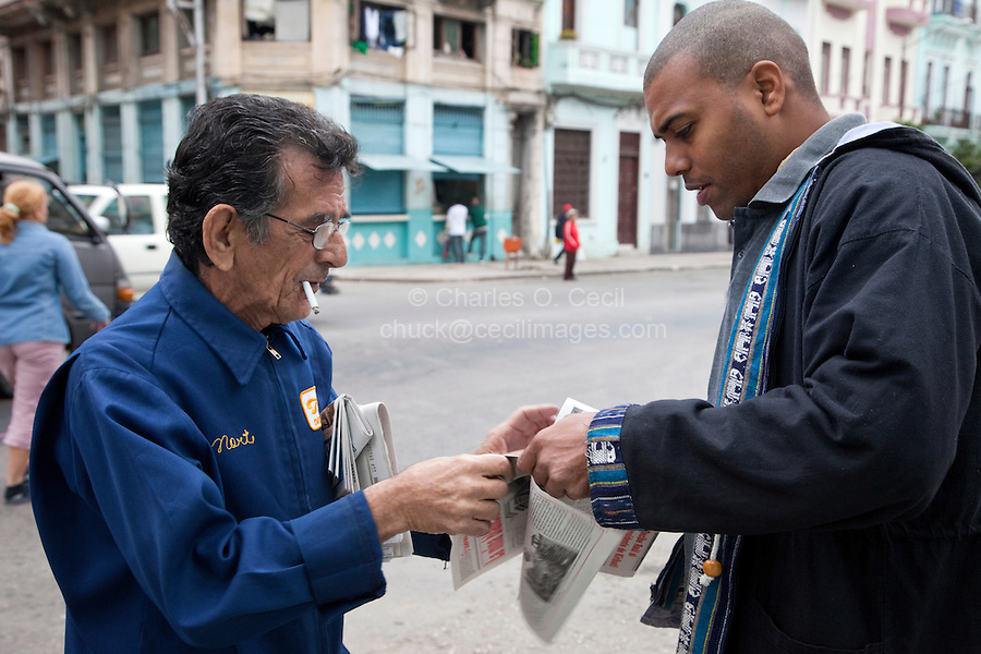 Cuba, Havana.  Newspaper Vendor Selling a Copy of Granma, the Official Newspaper of the Communist Party.