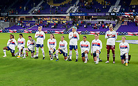 ORLANDO, FL - JANUARY 22: The USWNT stands and kneels during the national anthem before a game between Colombia and USWNT at Exploria stadium on January 22, 2021 in Orlando, Florida.