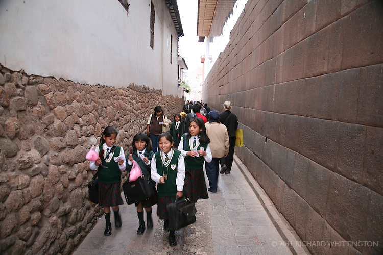 A group of schoolgirls walk down a street in Cuzco. The tone wall on the right is an original Inka wall over five hundred years old. Earthquakes continually topple Cuzco's colonial buildings while the Inka structures remain intact.