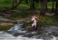 Teenagers enjoy the waters which are lined with Lingas at Phnom Kulen, Cambodia