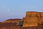 The soft light of dawn bathes one of the sides of the Pillars of Rome and surrounding sagebrush in Southeast Oregon with a purplish gentle pastel light as the full moon sets.
