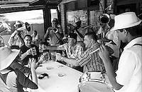 Festival di trombe e ottoni di Guca (Cacak). Delle persone sedute al tavolo di un ristorante fanno un brindisi con un boccale di birra mentre attorno suona una banda --- Trumpet festival of Guca (Cacak). People sitting at a table of a restaurant toast with a beer mug while a band is playing around them