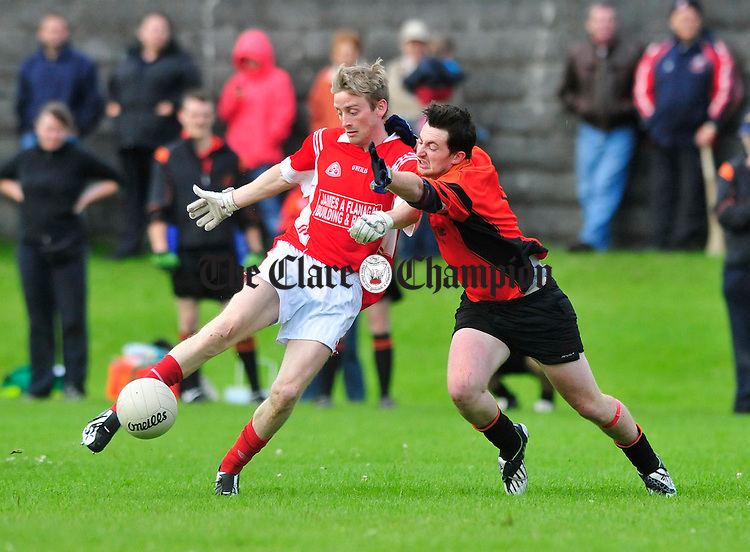 Corofin's Darragh Shannon clears under pressure from Ballyvaughan's Setanta Moran. Photograph by Declan Monaghan