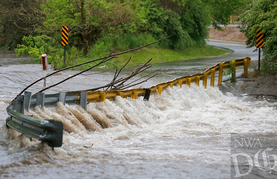 Water and debris run over the low water bridge Wednesday, April 28, 2021, on Ball Street in Johnson from Clear Creek. The National Weather Service office in Tulsa said the storm system that began moving through Northwest Arkansas Tuesday night had dropped from 1 to 3 inches of rain across the area by mid-morning Wednesday. With rainfall of 4 to 6 inches being reported in some areas. Check out nwaonline.com/210429Daily/ and nwadg.com/photos for a photo gallery.<br /> (NWA Democrat-Gazette/David Gottschalk)