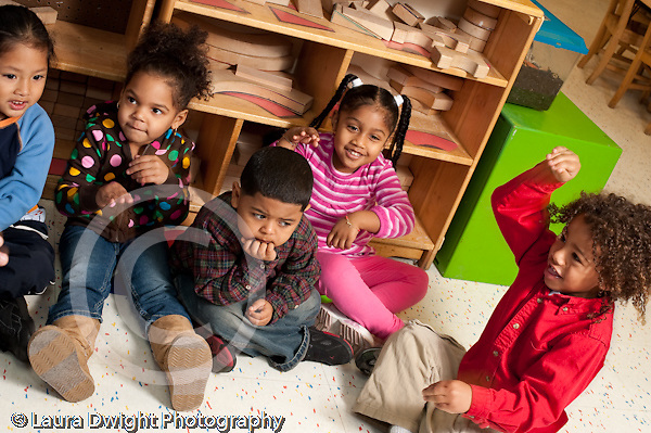 Education preschool 3-4 year olds circle time music song with gestures group participating one boy sad isolated not participating or joining in horizontal