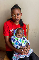 """Africa, DRC, Democratic Republic of the Congo, Goma, Lake Kivu,  Global Fund for Women. Stop violence in schools campaign by the PAIF organization project. Kisonga Matondo (17 yrs) is an orphan, her mother died at 3 months, her father when she was 8. At 13 she was raped by her 52 yr old teacher while in secondary school. She was afraid to tell anyone but she became pregnant, her baby is now 4 yrs old. The school did nothing. One day she was picked up by a man in his car, working on the boat transport system, who gave her a ride in the rain. He raped her. The baby she is holding is her second from a rape. When she became pregnant her took her in but beat her everyday, and she discovered she was his sixth wife and this was his 8th child. """"I suffered suffered suffered, but  had no one to take care of me until I met with PAIF."""" PAIF will help to sue her husband but if they lose he will kill her. There is no justice in this country."""
