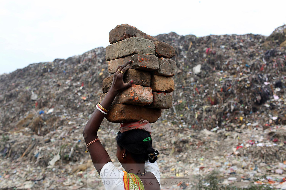 A woman carries bricks on her head at the Dhapa landfill in the west of Kolkata.<br />