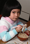 3 year old girl at home eating noodles w. chopsticks Asian American Chinese vertical