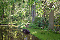 Woodland pond with small boat in water and dappled sunlight in environmentally-responsible, native plant sustainable garden, Mt Cuba Center Delaware