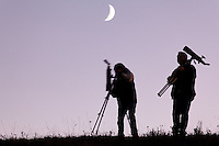 Wildlife watchers packing up at sunset under a crescent moon, Hayden Valley, Yellowstone National Park, Wyoming, USA