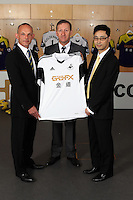 Pictured L-R: Albert SIn of Goldenway with club chairman Huw Jenkins and Albert Sin of Goldenway. <br /> Re: Official launch of the 2013-2014 Swansea City Football Club kit launch, with sponsors Goldenway GWFX at the Liberty Stadium, Swansea, south Wales. Friday 28th of June 2013