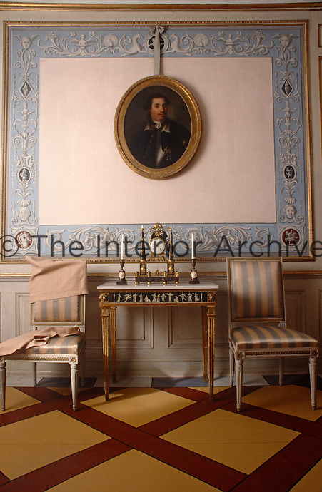 An oval gilt-framed portrait hangs from a ribbon against a hand-painted wall panel in this drawing room