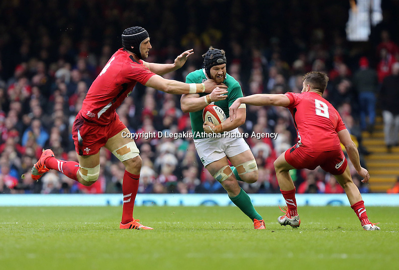 Pictured: Sean O'Brien of Ireland (C) is grabbed by Luke Charteris (L) and Rhys Webb (R) of Wales Saturday 14 March 2015<br /> Re: RBS Six Nations, Wales v Ireland at the Millennium Stadium, Cardiff, south Wales, UK.