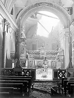 Pvt. Paul Oglesby, 30th Inf., standing in reverence before an altar in a damaged Catholic Church.  Note: pews at left appear undamaged, while bomb-shattered roof is strewn about the sanctuary.  Acerno, Italy.  September 23, 1943.  Benson. (Army)<br /> NARA FILE #:  111-SC-188691<br /> WAR & CONFLICT BOOK #:  1033