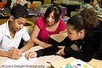 Education Elementary school Grade 5 class with science specialist making models from toothpicks and mini marshmallows making drawing on paper to plan how to make models two female and one male student working together horizontal