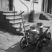 Ein Handkarren mit Milchkannen steht in einer Gasse in Deutschland, 1930er Jahre. A push cart with milk cans on a cobblestone lane in Germany, 1930s.