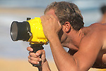 A man takes photographs with a underwater camera housing on Sandy Beach in Hawaii.