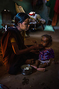 21 year old, Rekha RAMESH feeds boiled potatoes to her 18 month old Prahlad RAMESH, a recovering malnourished boy in their house in Dhawati VIllage of Khaknar block of Burhanpur district in Madhya Pradesh, India.  Photo: Sanjit Das/Panos for ACF