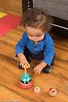 18 month old toddler boy playing with rings and spindle toy