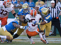UCLA defenders tackle Donovonn Young of Illinois during Kraft Bowl at AT&T Park in San Francisco, California on December 31st, 2011.   Illinois defeated UCLA, 20-14.