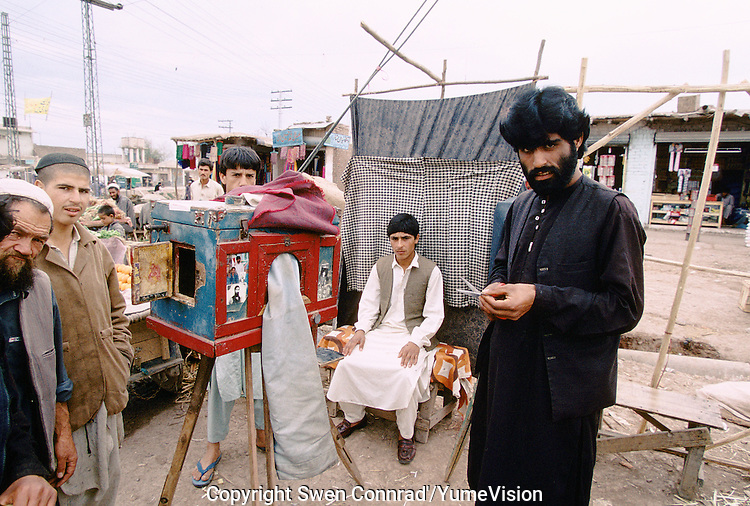A Pakistani photographer in a Afghan refugee camp in Peshawar, Pakistan