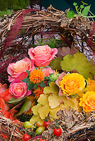 Harvest basket of apples fruits, roses, Heuchera, flowers, vegetables, autumn picked fall crops, from edible garden, cut flowers, arrangement, pretty variety of mixed plants