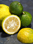 Whole and sliced yuzu, a yellow and green east Asian citrus fruit similar in appearance to lemon or lime.