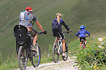 I took a brake from hiking, but not from taking pictures of the mountain bikers going by.  Digital cameras allow you to take many images for free, so you can get lucky sometimes. Note how the lines converge to the right, forming a pennant shape. <br />