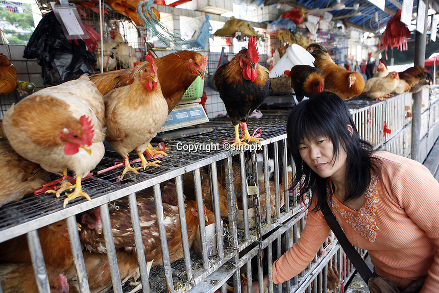 A woman feeds chickens in the Futian agriculture and produce market.<br />