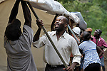Benoit Bernard helps lift a large tent being erected for use as a school classroom in the remote Haitian village of Embouchure. Bernard is director of the village's school, run by the Episcopal Church, which was damaged in the January 12, 2010, earthquake, but classes have continued to take place in the damaged structure. Villagers are now tearing down the old school to build a new one, and will use the tent classroom during the construction period. The school construction in Embouchure is funded by International Orthodox Christian Charities and FinnChurch Aid.