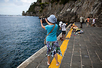 A tourist snaps a picture from the ferry dock on Sunday, Sept. 20, 2015, in Positano, Italy. (Photo by James Brosher)