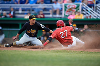 Batavia Muckdogs right fielder Jerar Encarnacion (27) slides into home plate as pitcher Michael LoPresti (43) reaches out to tag him during a game against the West Virginia Black Bears on June 19, 2018 at Dwyer Stadium in Batavia, New York.  West Virginia defeated Batavia 7-6.  (Mike Janes/Four Seam Images)