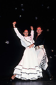 Argentina. Gaucho dancer with female partner in long white dress dancing the tango.